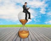 Man using smart pad sitting on sandglass — Stock Photo