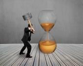 Hand hold hammer to strike hourglass — Stock Photo