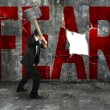 Постер, плакат: Businessman holding sledgehammer hitting red FEAR word on concre