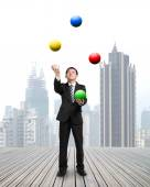 Businessman throwing and catching colorful balls — Stock Photo