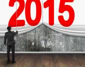 Businessman pulling down 2015 curtain to cover mottled concrete  — Stock Photo