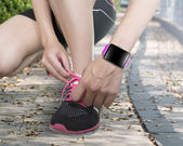Human hand tying shoelaces wearing smartwatch with bright pink w — Stock Photo