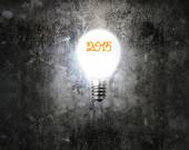 Bright 2015 light bulb illuminated dark old mottled concrete wal — Stock Photo