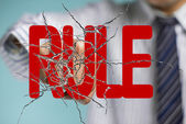 Businessman hand hitting red rule word on cracked transparent gl — Stock Photo