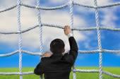 Businessman climbing crisscross rope net on sky cloud grass back — Stock Photo