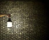 Hand holding vintage lamp illuminating dark brick wall — Stock Photo