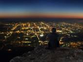Businessman sitting on rocky mountain with city night view — Stock Photo