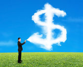 Businessman spraying dollar sign shape cloud paint with sky gras — Stock Photo