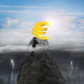 Businessman hand wanting euro symbol on peak with sunny stormy — Stock Photo