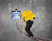 Businessman carrying gold jigsaw puzzle piece toward hole with s — Stock Photo