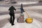 Man drawing golden sand currency symbols retro pump desert — Stock Photo