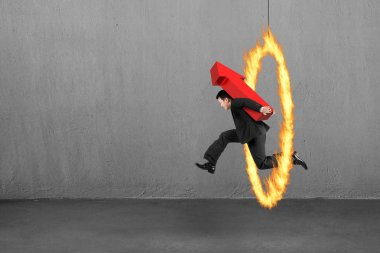 Businessman carrying red arrow up sign jumping through fire hoop