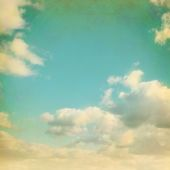 Old paper background with blue sky and white clouds in grunge style. — Stock Photo