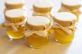 Stock Photo: Jar of honey on white table jam confiture marmalade pozzy  make conserve preserve — Stock Photo