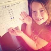 Girl showing weekly reward chart — Stockfoto