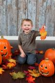 Little boy with autumn leaves and pumpkins — Foto de Stock