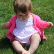 Little girl sitting on grass — Stock Photo #53352945