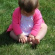 Little girl sitting on grass — Stock Photo #53352949