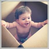 Little baby girl in shipping box — Stock Photo