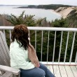 Woman looking from patio into ocean — Stock Photo #53381893