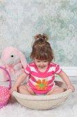 Beautiful Little Girl sitting in basket — Stock Photo