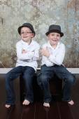 Boys wearing hats sitting in old empty room — Stock Photo