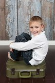 Cute boy sitting on suitcase — Stock Photo