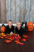 Boys with halloween pumpkins and yellow leaves — Stock Photo