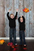 Little boys playing with autumn leaves — Stock Photo