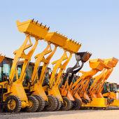 Die Zeile schwere Baumaschine Bagger gegen Blau sk — Stockfoto