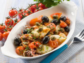 Squid with tomatoes olives and capers — Stock Photo