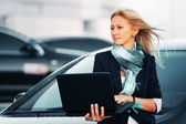 Fashion business woman with laptop on the car parking — Stock Photo
