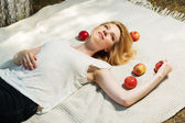 Happy young woman with apples lying on the cover — Stock Photo