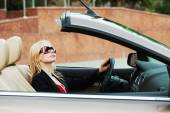 Happy young fashion woman driving convertible car — Stock Photo