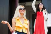 Two happy young fashion women with shopping bags — Stok fotoğraf
