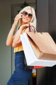 Happy young woman with shopping bags calling on the cell phone — Stock Photo