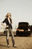Fashion woman with broken car calling on phone for help — Stock Photo