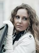 Fashion woman with long curly hairs at the car — Stock Photo
