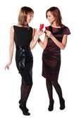 Two young fashion women with a red wine glasses — Stock Photo