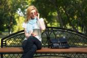 Young fashion woman using tablet computer in a city park — Stock Photo