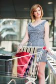 Young woman with shopping cart in the mall — Stock Photo