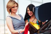 Two young women with shopping bags at the car — Stock Photo