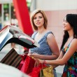 Two young fashion women with shopping bags at the car trunk — Stock Photo #58163763