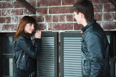 Happy young couple flirting at the wall — Stock Photo