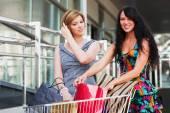 Two young fashion women with shopping cart — Stock Photo
