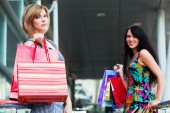 Two young fashion women with shopping bags — Stock Photo