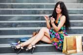 Genç ile alışveriş torbaları alışveriş merkezi basamaklarında oturan kadın moda — Stok fotoğraf