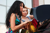 Two young fashion women with shopping bags at the car trunk — Stock Photo