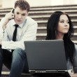 Young business couple using laptop outdoor — Stock Photo #62918511