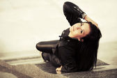 Happy young fashion woman lying on the city sidewalk  — Foto Stock